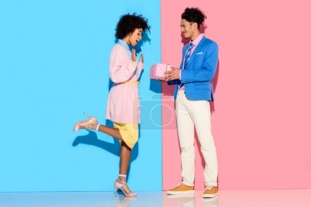 Young african amercian man gives girl gift box on pink and blue background