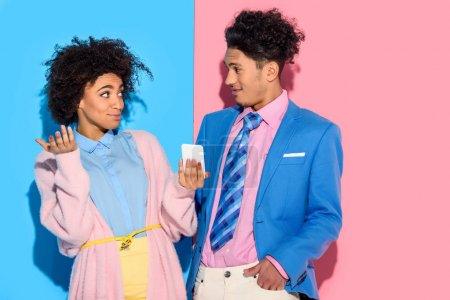 Young african amercian surprised girl showing man phone screen on pink and blue background