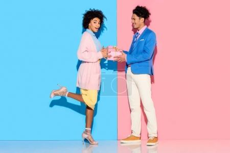 Young african amercian man gives girl gift box on pink and blue background on pink and blue background