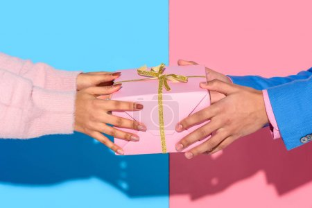 Close-up view of man giving girl gift box on pink and blue background