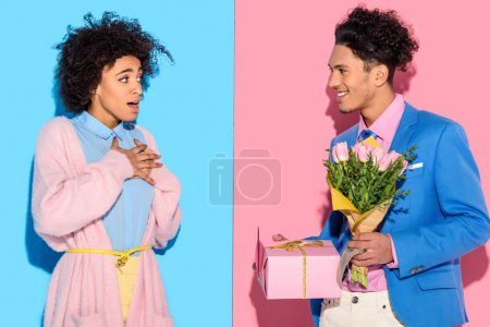 Young african amercian man gives surprised girl bouquet of flowers and gift box on pink and blue background