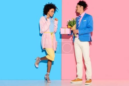 Smiling man presenting box and flowers to woman on pink and blue background