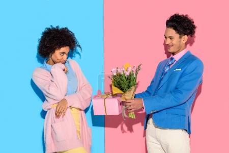 bel homme présentant la boîte et fleurs de femme sur fond rose et bleu