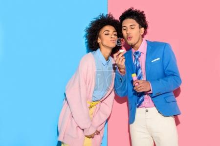 African couple having fun and blowing soap bubbles on pink and blue background
