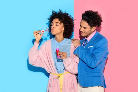 African couple having fun with soap bubbles on pink and blue background