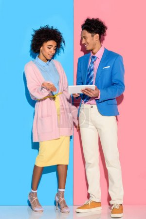 Happy couple using digital tablet on pink and blue background