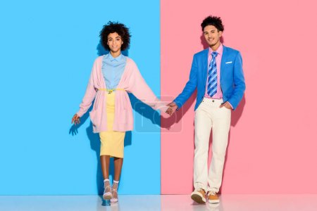 happey couple holding hands on pink and blue background