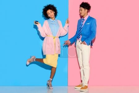 Young couple having fun on pink and blue background