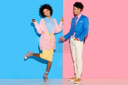 Photo for Young couple having fun on pink and blue background - Royalty Free Image