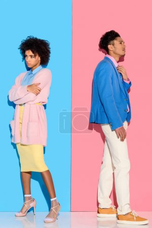 Pensive couple standing in distance of each other on pink and blue background