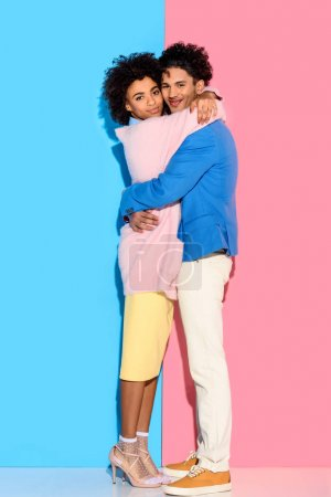 Photo for Young couple hugging each other on pink and blue background - Royalty Free Image
