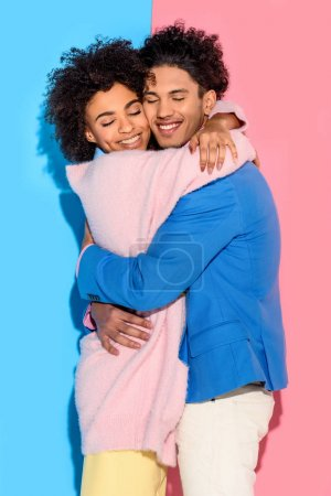 Photo pour Beau jeune couple se serrant dans ses bras sur fond rose et bleu - image libre de droit