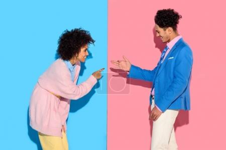 Happy couple gesturing and making funny shadows on pink and blue background