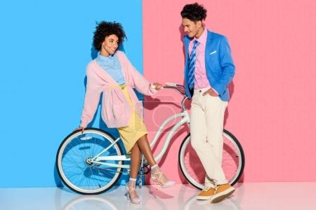Photo for Attractive couple having fun with bicycle on pink and blue background - Royalty Free Image