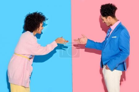 Smiling couple gesturing and making funny shadows on pink and blue background