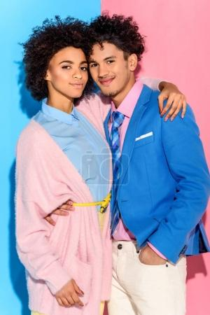fashionable young couple hugging each other on pink and blue background