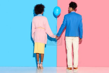Rear view of young couple holding hands with air balloon on pink and blue background