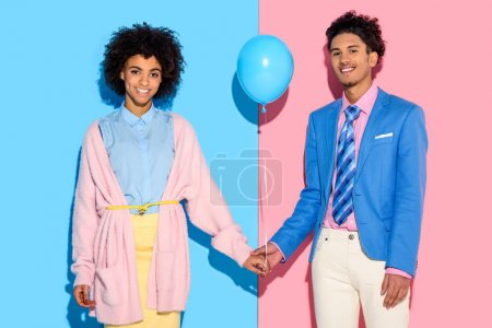 Young couple holding hands with air balloon on pink and blue background