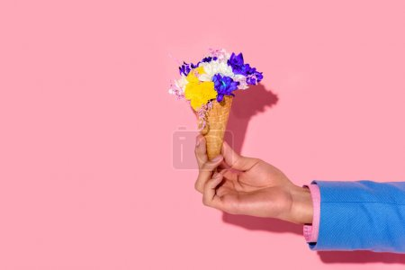 cropped shot of african american man holding flowers in ice cream cone on pink wall background