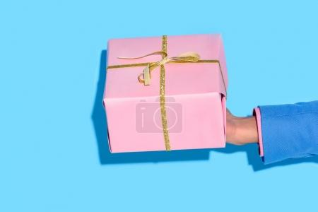 partial view of african american man holding wrapped gift on blue wall background