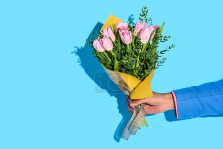 partial view of african american man holding bouquet of flowers on blue background