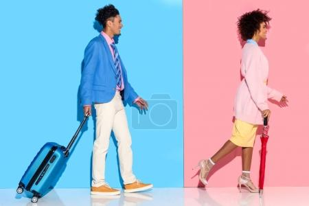 side view of african american couple with suitcase walking on pink and blue wall background