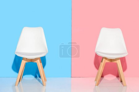 Photo for Close up view of white chairs against blue and pink wall - Royalty Free Image