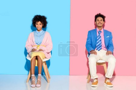 Photo for Smiling african american couple sitting on chairs against pink and blue wall backdrop - Royalty Free Image
