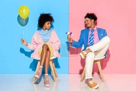 Photo for African american man presenting flowers in ice cream cone to girlfriend while sitting on chairs against pink and blue wall backdrop - Royalty Free Image
