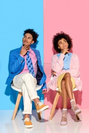 african american pensive couple sitting on chairs against pink and blue wall backdrop