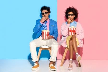 young african american couple sitting on chairs and eating popcorn against pink and blue wall