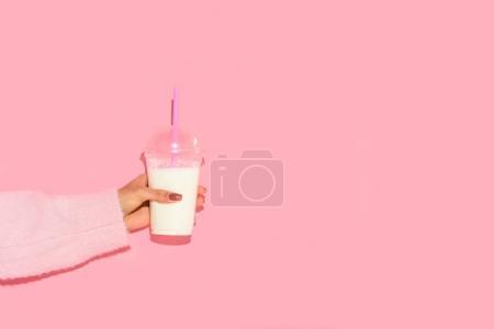 Photo pour Vue partielle de la femme afro-américaine tenant un verre de lait avec de la paille contre un mur rose - image libre de droit