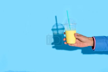 Cropped shot of african american man holding glass of juice on blue background