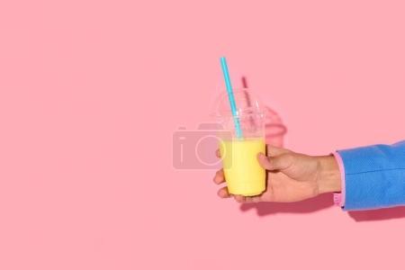 Photo pour Plan recadré de l'homme afro-américain tenant un verre de jus sur fond rose - image libre de droit