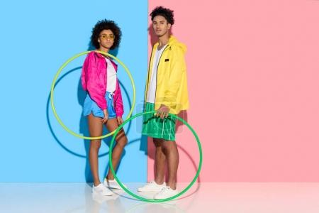 Young couple standing with hoops and looking to camera on pink and blue background