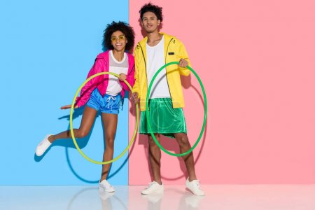 Sporty couple standing with hoops and looking to camera on pink and blue background