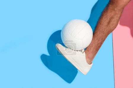 Cropped image of leg with ball  on pink and blue background
