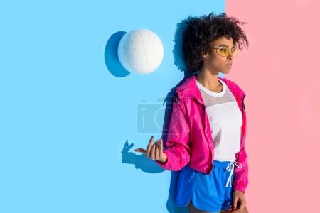 Photo for Attractive girl standing against wall and throwing up ball on pink and blue background - Royalty Free Image