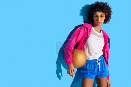 Young girl in glasses holding basketball ball and looking away on blue background