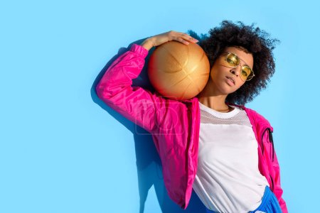 Photo for Young girl in glasses holding basketball ball and looking at camera  on blue background - Royalty Free Image