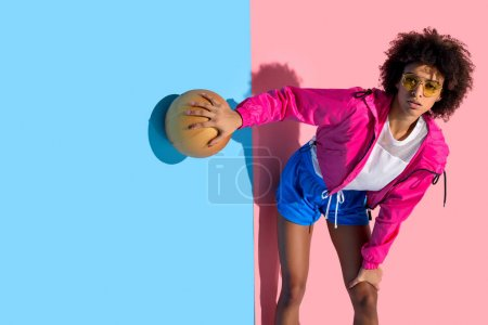 Young girl in glasses holding basketball ball and looking away  on pink and blue background