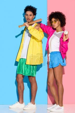 Photo pour Séduisante jeune couple avec équipement de baseball en mains regardant la caméra sur fond rose et bleu - image libre de droit
