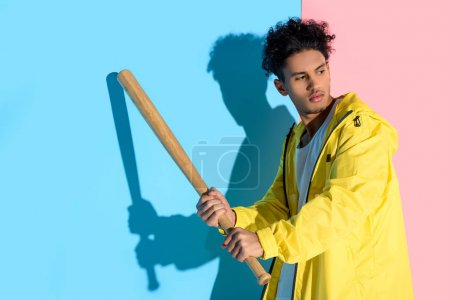 Handsome young man holding baseball bat in hands about to kick and looking away on pink and blue background