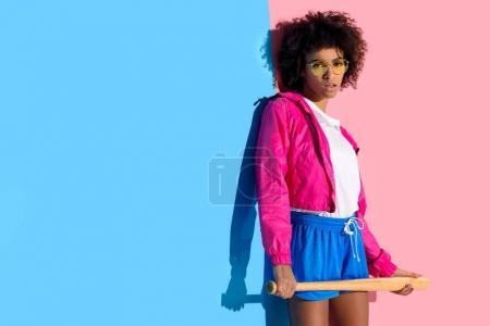 Young bright african american girl holding baseball bat