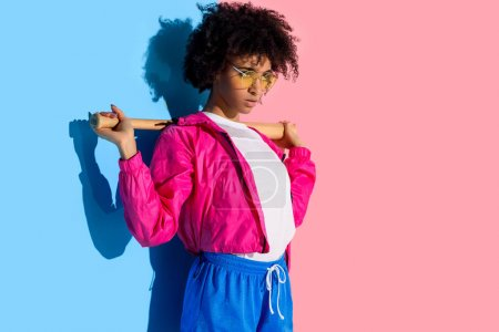 Young bright african american girl with baseball bat on her shoulders on pink and blue background