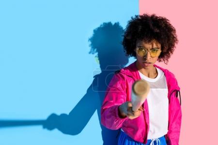 Photo for Young angry african american girl pointing in camera with baseball bat on pink and blue background - Royalty Free Image