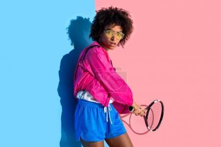 Foto de Joven afroamericana brillante cambios de raqueta de tenis sobre fondo rosa y azul - Imagen libre de derechos