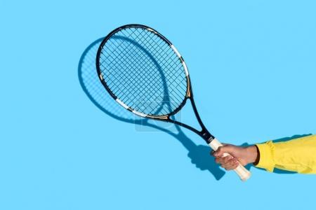 Close-up view of male hand holding tennis racket on blue background
