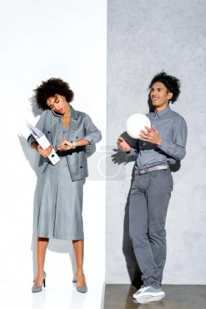 Young african amercian busy businesswoman holding folder and talking on phone while relaxed guy playing with ball on grey and white background