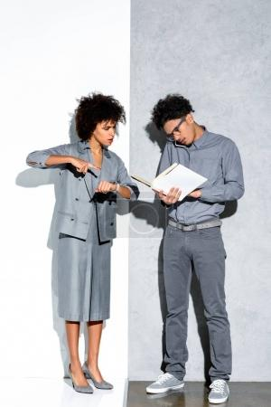 Young african amercian businessman holding folder and talking on phone while angry businesswoman pointing on watch on grey and white background